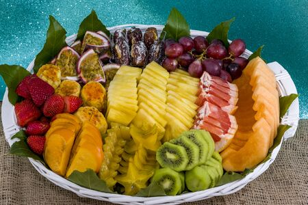 Healthy fresh fruits in a basket on table Sliced fruits in a basket kiwi pineapple strawberry.