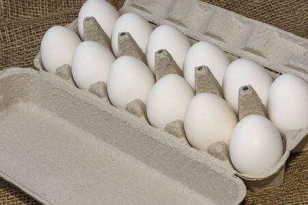A dozen white eggs against a background of burlap chicken eggs, closeup photo, April 18, 2020