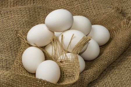 White chicken eggs wrapped in burlap next to a basket on a White eggs on burlap background Banco de Imagens