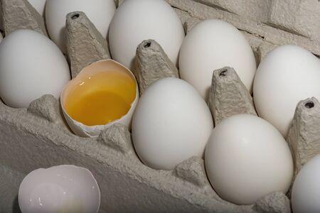 White eggs in carton with broken egg A dozen white eggs
