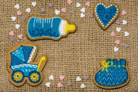 Cookies on a burlap in the form of a stroller in a bottle of baby hearts. Baby shower cookies on table Banco de Imagens