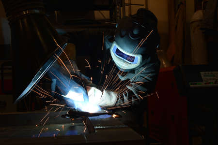 worker with protective mask welding metal and sparks. The welder is welding metal.