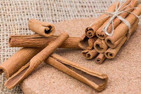 cinnamon sticks, Dry cinnamon bark tied in a bunch on a burlap background.