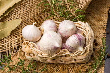 Garlic Cloves and Bulb in vintage wooden bowl. Garlic