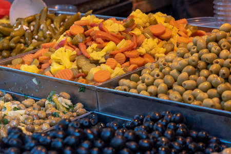 Pickles (olives, carrot and yellow cauliflower) on a white plate and a blue table - close, Salting olives carrots cauliflower.