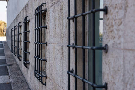 Old Window With Rusty Forged Bars In White Wall Background. The windows are in a row with massive black bars.