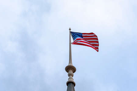 American flag waving in blue sky. American flag at the top. Banque d'images