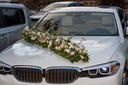 wedding decoration of a car from a flower arrangement, on the hood of a car, white car with wedding flowers on the hood