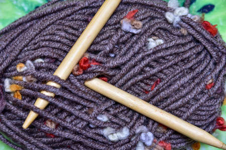 Knitting needles and a ball of woolen thread on a dark gray wooden background. dark wooden threads and knitting needles Banque d'images