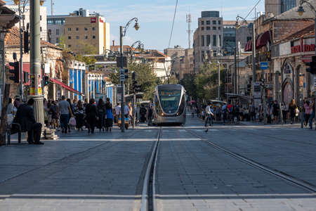 JERUSALEM, ISRAEL, 11/13/2020. Tramway in the city center, new technology transportation with pedestrians on the street.