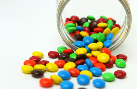 smarties: Colorful sugar-coated chocolate smarties in a glass jar on a white background Stock Photo