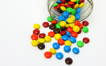 Colorful sugar-coated chocolate smarties in a glass jar on a white background Stock Photo