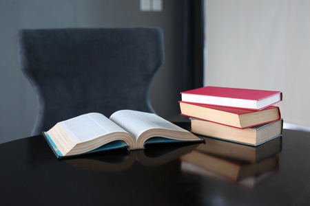 hardcover: Open book and stack of hardcover books on wooden table.