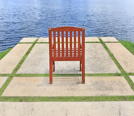 insular: The old red brown wooden chair alone in the park