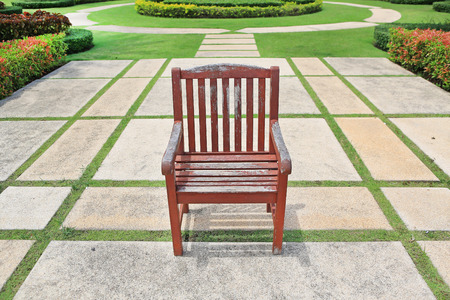 singly: The old red brown wooden chair alone in the park