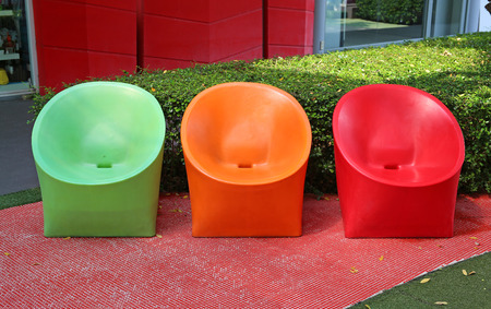Multi-colored plastic chairs in the garden. Stock Photo
