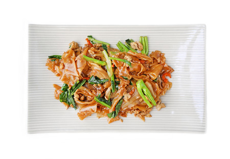 Stir fried flat noodle and pork with dark soy sauce on white background