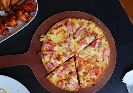 Hawaiian pizza on a wooden tray