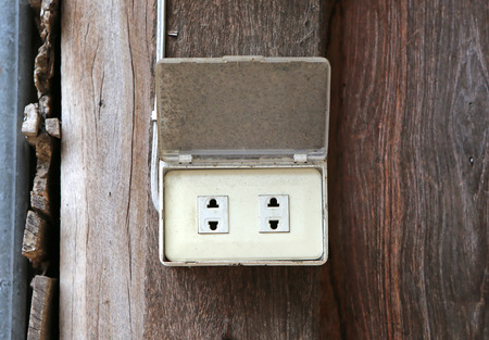 grounded plug: old electrical outlet on wood wall.
