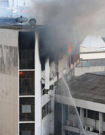 tragedies: flames and smoke rise from burning building