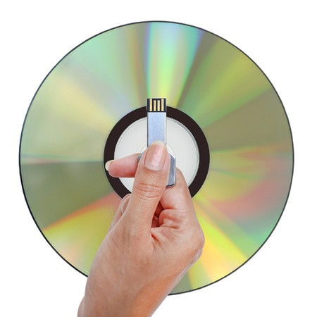 Hand holding USB data storage against disk DVD CD on white background. Archivio Fotografico
