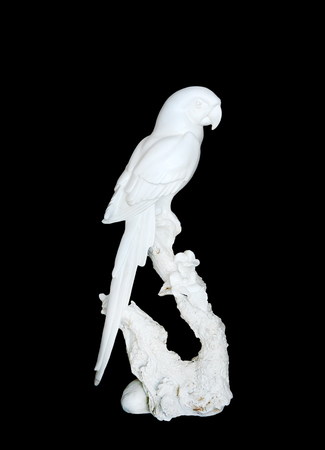 Statue of white parrot isolated on black background