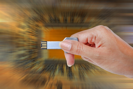 Key USB data storage in hand against bright light and circuit background.