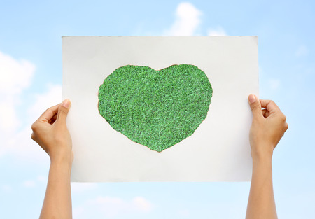 Hands holding paper art sheet Burning in shape of heart with image of green grass against Cloud sky. Stock Photo