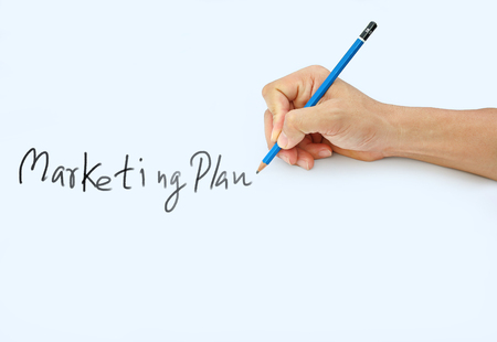 Hand holding a pencil on a white paper background, writing with pencil for word  Marketing Plan