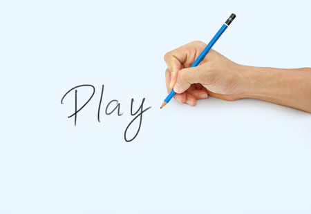 Hand holding a pencil on a white paper background, writing with pencil for word  Play  Stock Photo