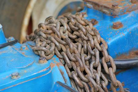 Pile of old rusty chain on part of tractor