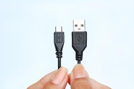 白い背景の上のマイクロ usb ケーブルに USB を持っている手