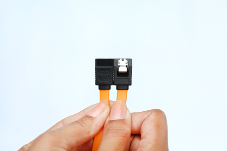 Hands holding sata data cable on white background