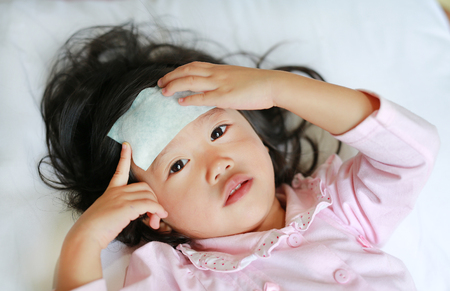Sick girl lying on the bed with a cool jell on her head, Medical and health care concept.