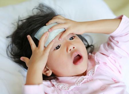 病気の女の子のクールなベッドの上に横たわる彼女の頭、医療と健康医療のコンセプトにゼリー状になります。