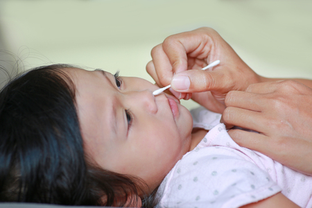 nose picking: Mother Cleaning Baby Ear With cotton swab.