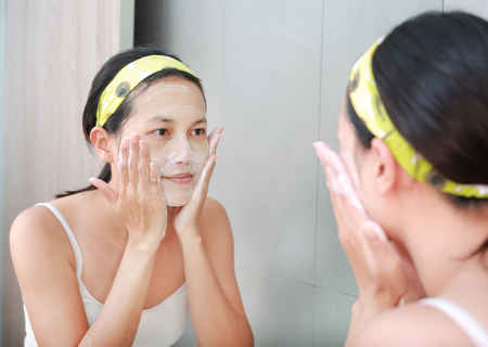 reflect: Woman applying foam cream to face reflect with bathroom mirror.