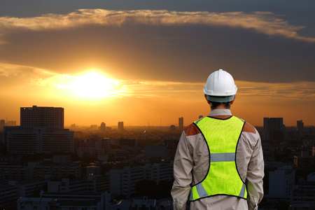 Back view of Male construction worker against building at sunset in bangkok city background Stock Photo