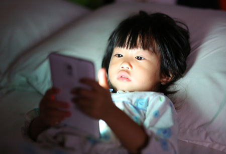 Kid girl playing smartphone lying on a bed at night Archivio Fotografico