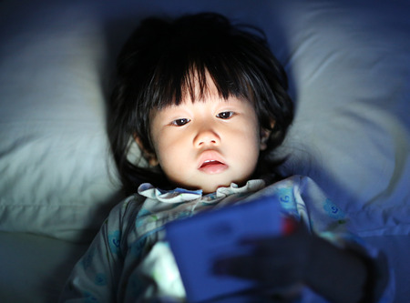 Kid girl playing smartphone lying on a bed at night Foto de archivo