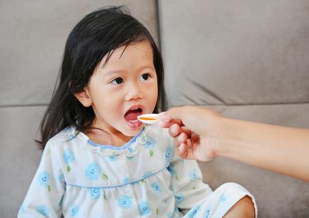 Cute little Child girl receiving pill at home Standard-Bild