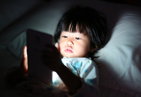 Kid girl playing smartphone lying on a bed at night Standard-Bild