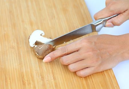 Sharp knife on woman hands cut Shiitake mushroom on wooden block