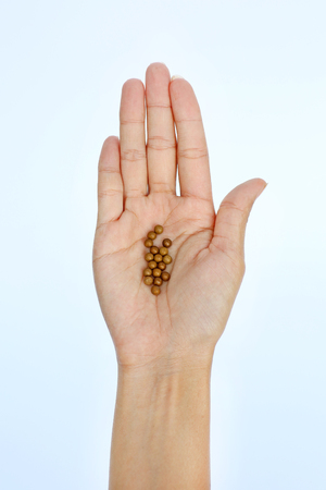 A hand of a woman with some lozenge pills on white background