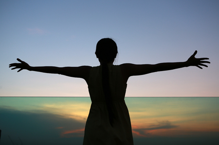 Silhouette of woman stretching arms enjoy relax at sunset on rooftop of the building Stock Photo