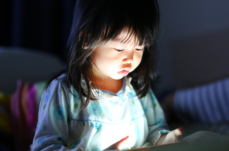 Cute little girl in pajamas playing smartphone lying on a bed