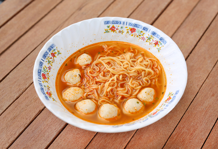 Instant noodles with meat balls in ceramic bowl against wooden plank.