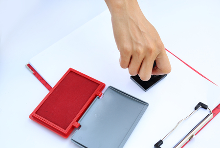 Hand holding rubber stamper with red Ink pad(box) on white paper.