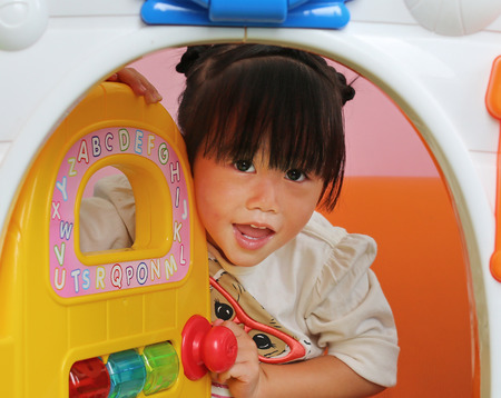 Little asian kid girl playing toy house.