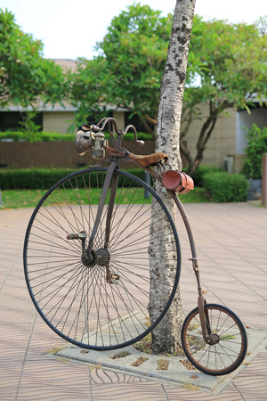 Retro bicycle with large front wheel in public park.